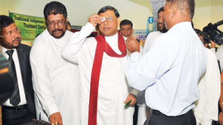 Economic Development Minister Basil Rajapaksa examines a pair of lenses at the opening of the Ayurveda Expo 2013 exhibition held at the BMICH last week. The event drew large crowds. Picture by Thushara Fernando
