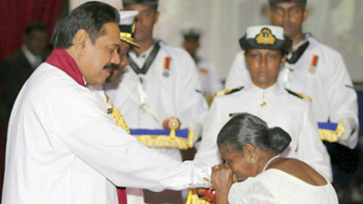 A mother of a War Hero who made the supreme sacrifice during the Wanni Humanitarian Operation in the attempt to free the nation from three decades of terrorism receiving the Weera Wickrama Padakkama from President Mahinda Rajapaksa awarded to her son, at the ceremony at the Temple Trees yesterday evening. Picture by Sudath Silva