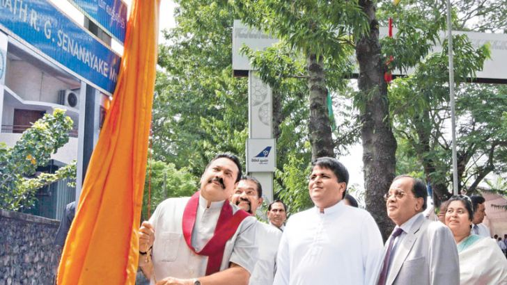 President Mahinda Rajapaksa unveils the name board to rename Gregory's Road, Colombo 7, R.G. Senanayake Mawatha yesterday. Colombo Mayor A.J.M. Muzammil and members of the R.G. Senanayake family were also present. Picture by Chandana Perera