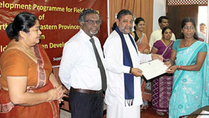 Child Development and Women's Affairs Minister Tissa Karaliyadda presenting a certificate to a field officer.