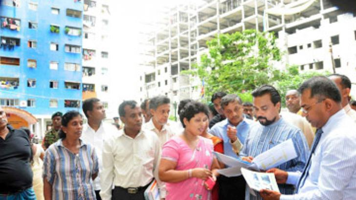 Construction, Engineering Services, Housing and Common Amenities Minister Wimal                 Weerawansa examining plans of housing development and renovation projects.