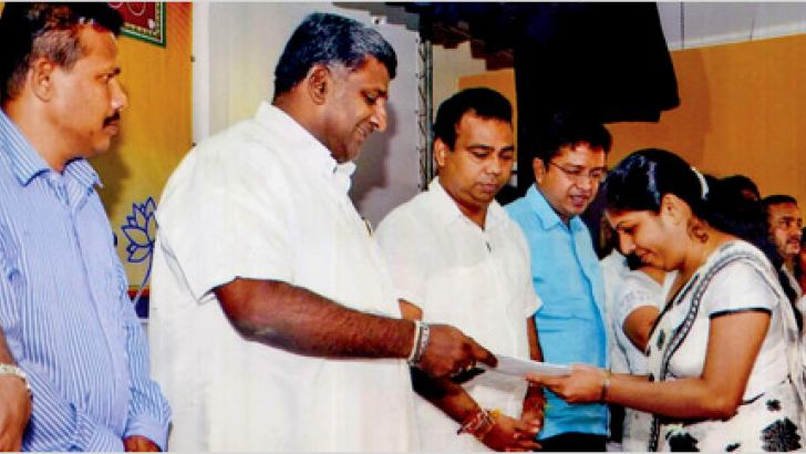 Western Province Chief Minister Prasanna Ranatunga handing over an appointment letter to a teacher recruit at a ceremony held at the Sravasthi Auditorium. Provincial Councillors Mahesh Almeida and A D Jagath Kumara are also in picture. Picture by Colombo Central Group Corr