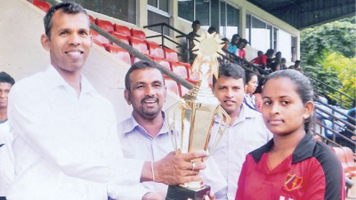 Nawanjana Ekanayake of Sangamitta Girls College, Matale, receiving the championship trophy from the chief Guest Athula Jayawardena – Director of Sports, Department of Education Central Province. Also in the picture Indrawansa Herath Secretary Sri Lanka Schools Hockey Association and Umpire Palitha Wasalege.