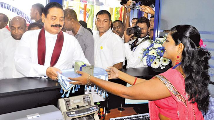 President Mahinda Rajapaksa opened a branch of the Sri Lanka Savings Bank in Matara. Here the President accepting the first deposit from a customer and handing it over to the branch manager Pradeepa Pushpa Kanthi. Picture by Sudath Malaweera