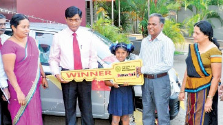 Assistant General Manager of People's Bank(Wayamba Zone) N.G Dissanayake handing over the vehicle to S.B Kokwewa, Kurunegala Reginol Manager N.A.C.W.K Nissanka and Kokwewa's wife and daughter are also present.