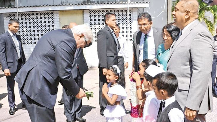 German's Federal Minister for Foreign Affairs Dr. Frank Walter Steinmeier is greeted by Sri Lankan children on arrival at the Foreign Ministry in Colombo yesterday. Looking on are Foreign Affairs Minister Mangala Samaraweera and Deputy Minister Dr. Harsha de Silva