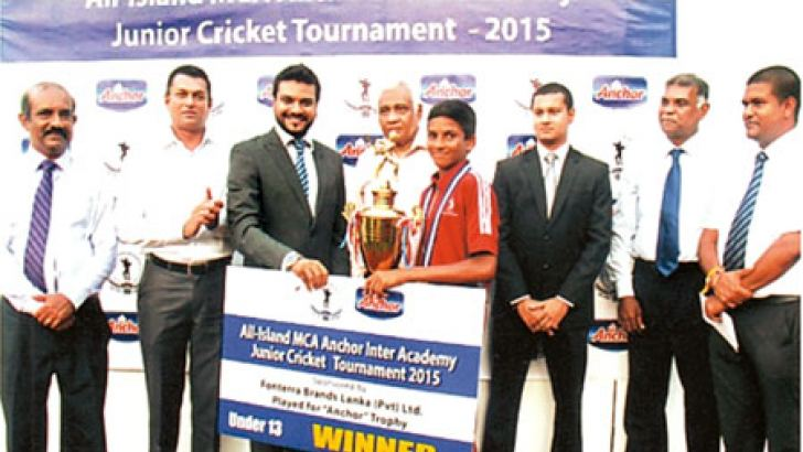Skipper of the CCC School of Cricket 'A' team Kavindu Pathiratne receives the champions trophy and the cash prize.