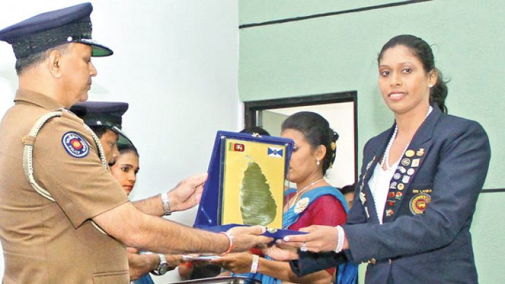 P.A.V.Chamarika is being rewarded by the Inspector General of Police N.K.Illangakoon for her excellence in overseas Netball and Volleyball events at the felicitation ceremony held at Police Crime Records Division, Colombo yesterday. Picture by Sudam Gunasinghe