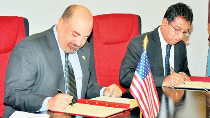 US Ambassador Atul Keshap and Deputy Minister of Foreign Affairs Dr. Harsha de Silva signing the MoU. Picture by Gayan Pushpika