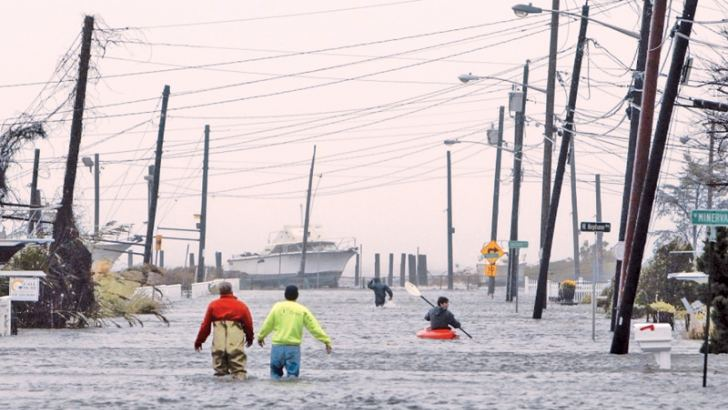 People wade and paddle down a flooded street when the town of Lindenhurst, New York was hit by Hurricane Sandy on October 29, 2012. File Photo