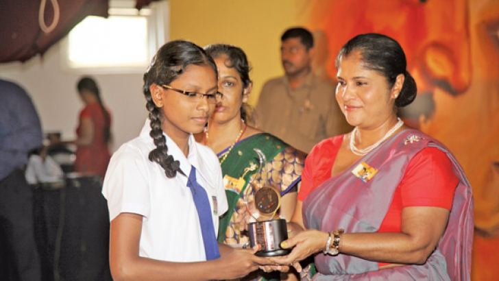 Women and Child Affairs Minister Chandrani Bandara hands over an award to a winner of the art and poster competition