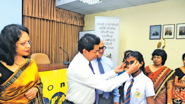 Health Services Di​rector General Dr. Palitha Mahipala helps a child to wear a new pair of spectacles while others look on.