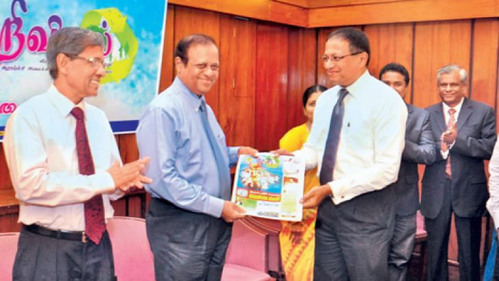 """ANCL Chairman and Managing Director Kavan Ratnayaka presenting the first copy of """"VIDYA"""", the bilingual publication of the Science, Technology and Research Ministry to Minister Susil Premajayantha at the launch held at the ANCL Boardroom yesterday. Picture by Lalith C.Gamage"""