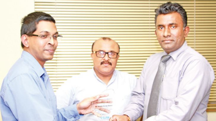 Student Nilendra Malaka being felicitated by SLIM President Ruwan Liyanagamage accompanied by Senior Lecturer G S Sylvester