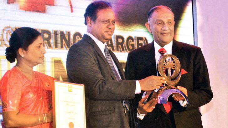 The Sri Lanka National Quality Awards, an annual Award to recognize organizations that excel in quality management and quality achievement was held at the BMICH yesterday. Maliban Biscuit Manufacturers won the Gold award for Manufacturing (Large) category. Here Science Technology and Research Minister Susil Premjayanth presenting the award to Maliban Biscuit Manufacturers Chairman, Ratnapala Samaraweera. Picture by Ranjith Asanka