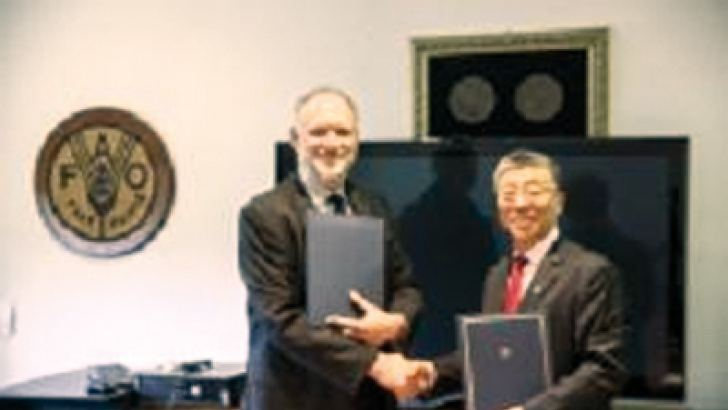 Two key officials from FAO and Mars exchanging the agreement