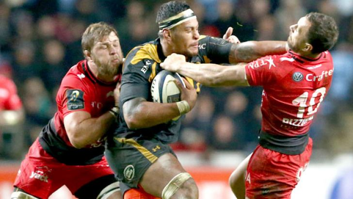 Wasps' number 8 from  Fiji Nathan Hughes is  tackled by Toulon's flanker  from South Africa Duane  Vermeulen (L) and Toulon's  fly-half from Australia Quade  Cooper (R) during the European Rugby Champions Cup  rugby union match between Wasps and  Castres.  AFP
