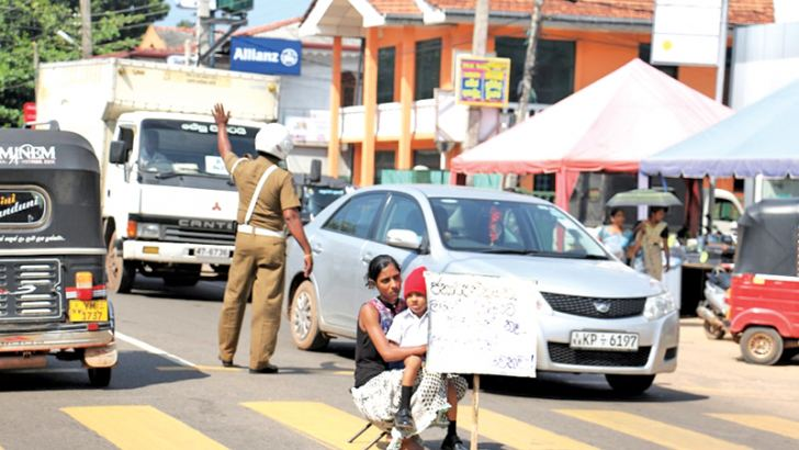 A mother sitting in the middle of the road with her son opposite Ananda National School, Chilaw protesting against the failure of the school authorities to admit her son. The mother who lives close to the school alleged that the school authorities are requesting money to admit her child. She said  both she and her husband too are past pupils of the school. Picture by Prasad Poornamal