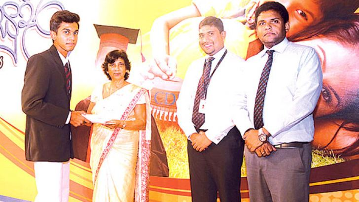 A student receiving his scholarship from chief guest Consultant Child Psychiatrist Prof. Hemamali Perera