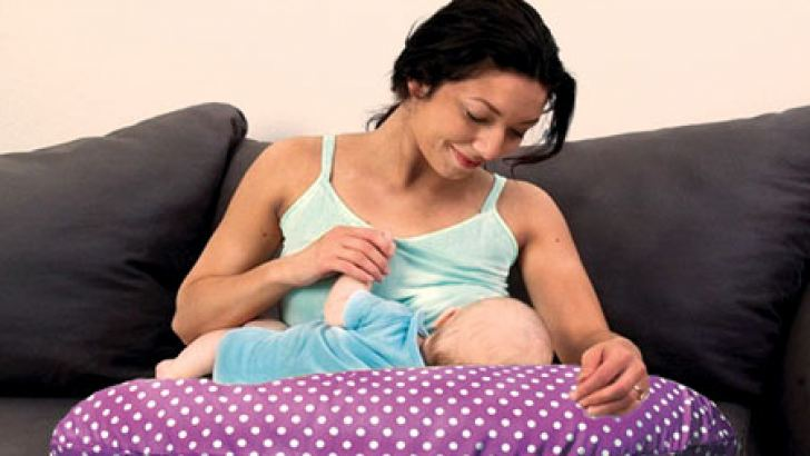 A Nursing Pillow being used to feed a baby