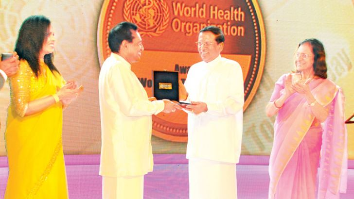 The World Health Organization awarded the World No Tobacco Day Award for 2010 to Health Minister Dr. Rajitha Senaratne in recognition of his role in mitigating the ill effects of tobacco, particularly smokeless tobacco. The Organization also recognized the Minister for advancing the introduction of pictorial health warnings on cigarette packs and the effort to obtain court approval for this purpose. Picture shows Minister Dr. Rajitha Senaratne receiving the award from President Maithripala Sirisena at a cer