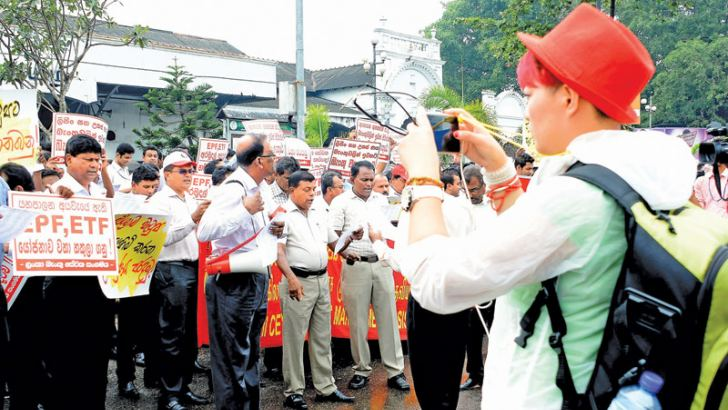 The Ceylon Federation of Trade Unions yesterday staged a protest opposite the Fort Railway station calling for the government to stop creating a Pension Fund by merging the EPF and ETF. Picture shows a foreigner capturing a photograph. Picture by Saman Mendis