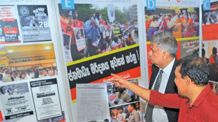 Prime Minister Ranil Wickremesinghe viewing an art exhibition at the BMICH yesterday, one of the events organised by the Nidahase Wedikawa  (Platform for Freedom) and the Civil Society to mark International Human Rights Day. Attorney-at- law Sudharshana Gunewardene is also in the picture. Picture by Rukmal Gamage