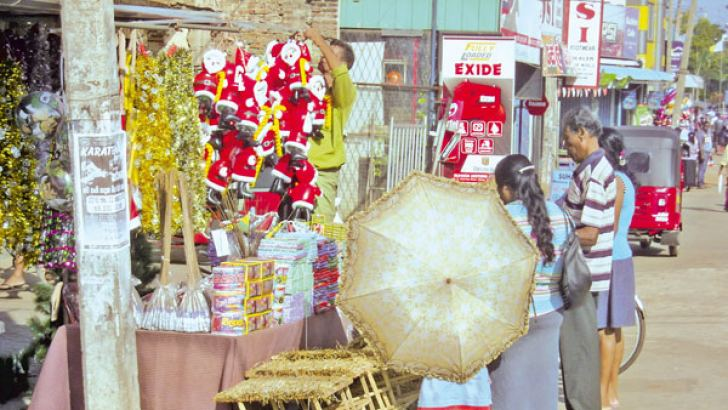 The 'crib' is an important segment of decorations in Christian homes during the Christmas season. Here, pavement hawkers in Chilaw making brisk sales of cribs designed for the occasion yesterday. Picture by Munneswarama group corr.