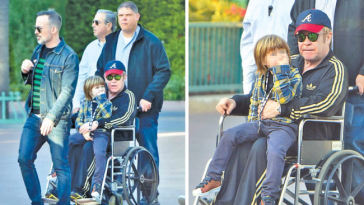 Elton John is pushed around disneyland in a wheelchair while spending a day with his kids and husband David Furnish. Elton enjoyed himself with his family for about four or five hours at the park and ended up being pushed in a wheelchair in the latter part of the day as he seemed to have gotten tired. his little guy zachary didnt seem to mind as he took a ride with his father