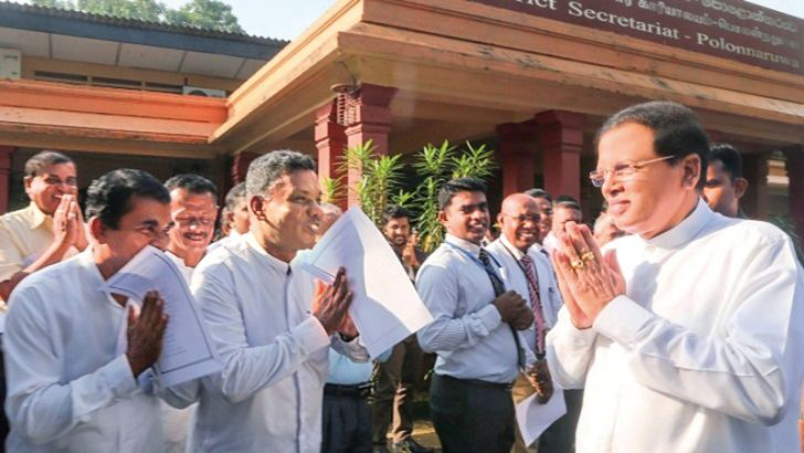 The staff of Polonnaruwa District Secretariat greets President Maithripala Sirisena on his arrival there.