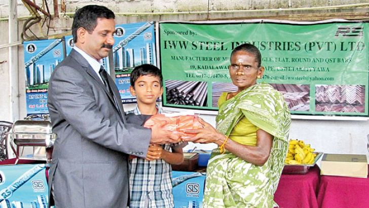 Dr. Shivalingam Ramesh, Chairman, IWW Steel handing over school items to a worker at the New Year celebrations of the company.