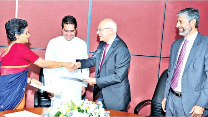 EDB Chairperson and CEO Indira Malwatte and SLINTEC Chairman Dr Mahesh Amalean exchange the MoU. International Trade State Minister Sujeewa Senasinghe and SLINTEC CEO Harin de Silva Wijeyeratne look on.