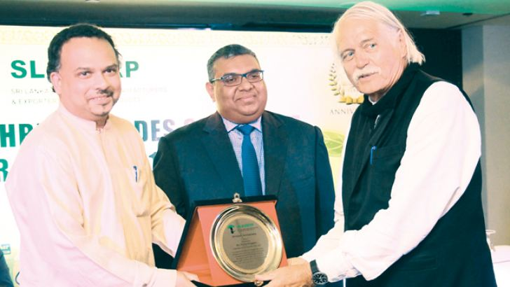 Two awards were  presented to N. G. Wickramaratne and P. G. J.  M. G. Pringiers  to appreciate the dynamic leadership and guidance provided by by them over the past three decades. Here  Pringiers receiving the award from the  Minister of Plantation Industries Navin Dissanayake looked on by SLAMERP Chairman, Prabhash Subasinghe.