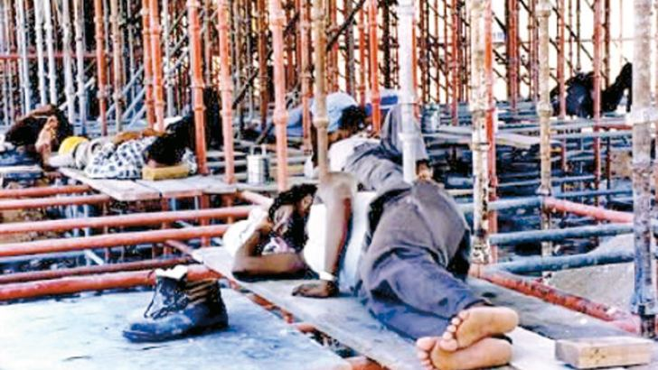 Workers take a rest during a break in a building under construction in  Dubai. File picture