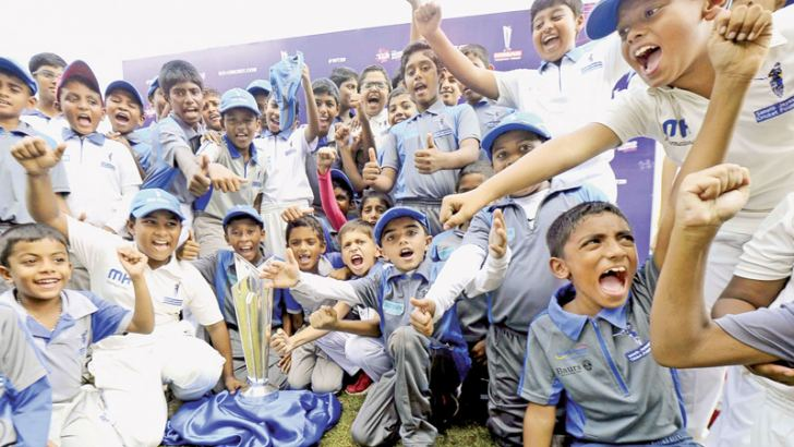 School children were given a chance to pose for photographs with the T20 World Cup as it arrived at SLC yesterday. Here youngsters cherishing the moment