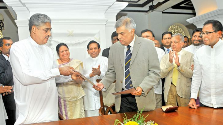 The United National Front yesterday entered into an agreement with the Democratic Party led by Field Marshal Sarath Fonseka at Temple Trees. Here, Prime Minister Ranil Wickremesinghe and Field Marshal Sarath Fonseka exchanging the documents. Picture by Rukmal Gamage