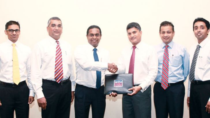 LankaClear General Manager and CEO Channa de Silva exchanging the agreement with HSBC COO Sriyan Cooray while HSBC Corporate Banking Head Chamira Wijetilleke, LankaClear IT and Operations Deputy General Manager Harsha Wanigatunga, HSBC  Retail Banking and Wealth Management Head Nilantha Bastian and LankaClear Help Desk Senior Manager Isuru Jayaweera look on.