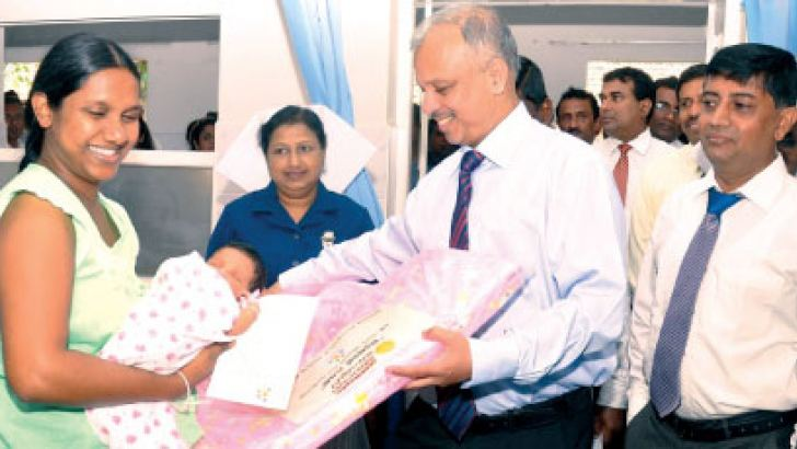 People's Bank Chief Executive Officer and  General Manager N. Vasantha Kumar offering a gift to a newborn baby at the Castle Street Hospital.