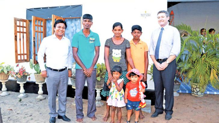 World Vision Lanka National Director Jonathan Johnson with  U.L. Nimani Sunethra Malkanthi and her family supported by the project to complete their home in Mudalama) and  Holcim Lanka  CEO Philippe Richart  a member of the Lafarge Holcim group.