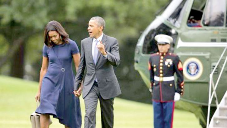 President Barack Obama and First Lady Michelle Obama walk across the South Lawn of the White House in Washington. - AFP