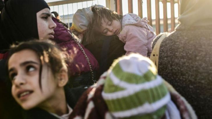 Syrian families line-up on Thursday at the Turkish Oncupinar border gate near Kilis, southern-central Turkey. - AFP