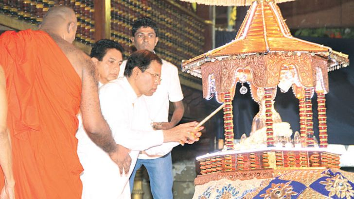 President Maithripala Sirisena yesterday evening placed the Sacred Relics Casket on the ceremonial tusker on the first day of the Gangarama Temple's Navam Perahera.  Picture by Ruwan De Silva