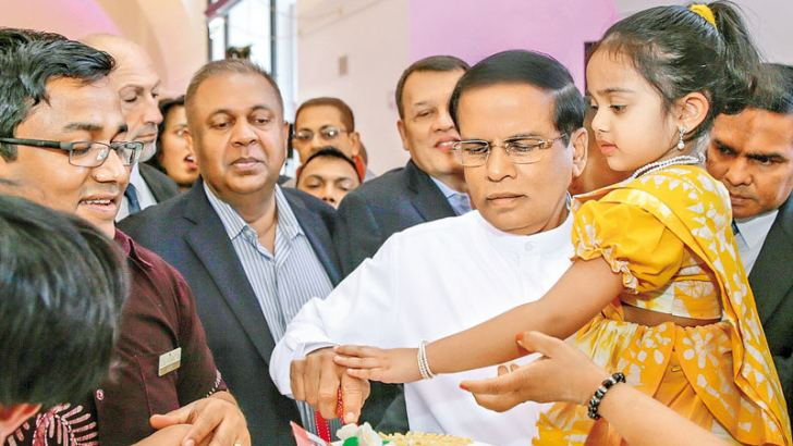 President Maithripala Sirisena met the Sri Lankan community in Vienna, Austria on Saturday. Here the President is seen carrying a small Lankan girl dressed in a saree while cutting a cake. Also in the picture are Ministers Mangala Samaraweera and Mahinda Samarasinghe
