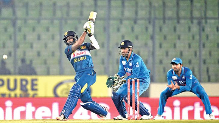 Sri Lanka's Chamara Kapugedera (L) plays a shot as Indias captain Mahendra Singh Dhoni (C) looks on during the Asia Cup T20 cricket tournament match between India and Sri Lanka at the Sher-e-Bangla National Cricket Stadium in Dhaka on March 1. AFP