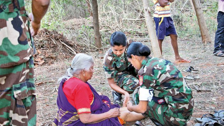 An elderly woman being attended to by the Army women's corp members
