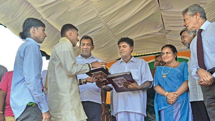 Minister Sajith Premadasa handing over deeds of land to a beneficiary in the Thurunugama village. Picture by A.A.L. Dias, Matale District Group Corr.