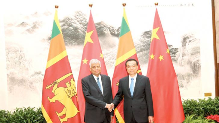 Chinese Premier Li Keqiang welcomed Prime Minister Ranil Wickremesinghe at a state ceremony in Beijing yesterday. The  picture shows Premier Li receiving Prime Minister Wickremesinghe
