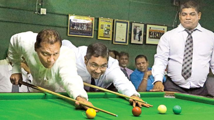Sports Minister Dayasiri Jayasekera (extreme left) potting the ball after he opened the new billiards table of the Automobile Association of Ceylon on Thursday. Picture by Saman Sri Wedage.