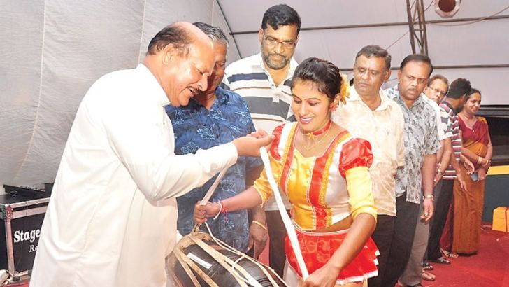Central Province Chief Minister Sarath Ekanayake hands over a traditional drum to one of the students of the Vidyalaya.