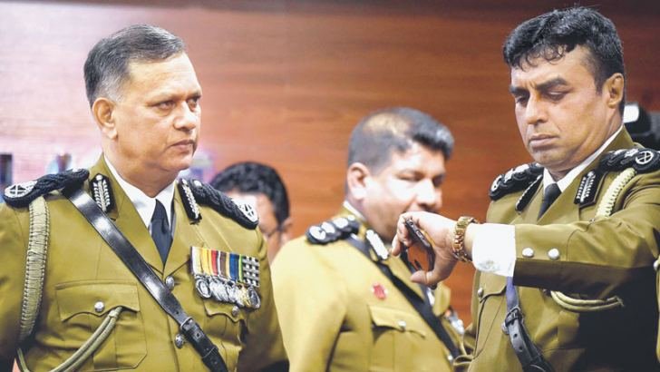 Outgoing IGP N.K.Illangakoon (L) looks on as Senior DIG Pujith Jayasundara checks his watch at police headquarters in Colombo yesterday ahead of starting his final meeting with officers and men. - AFP